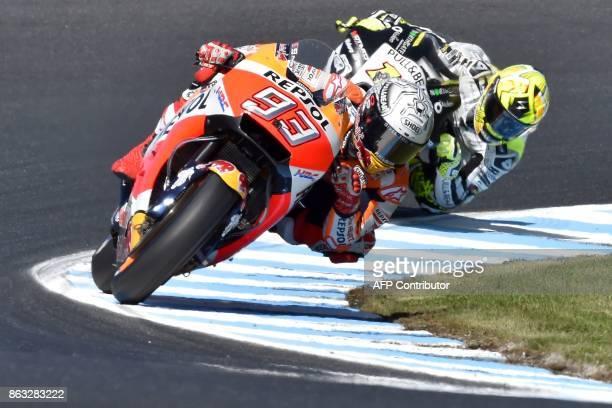 Honda rider Marc Marquez of Spain powers ahead of compatriot PullBear Aspar rider Alvaro Bautista during the first practice session of the Australian...