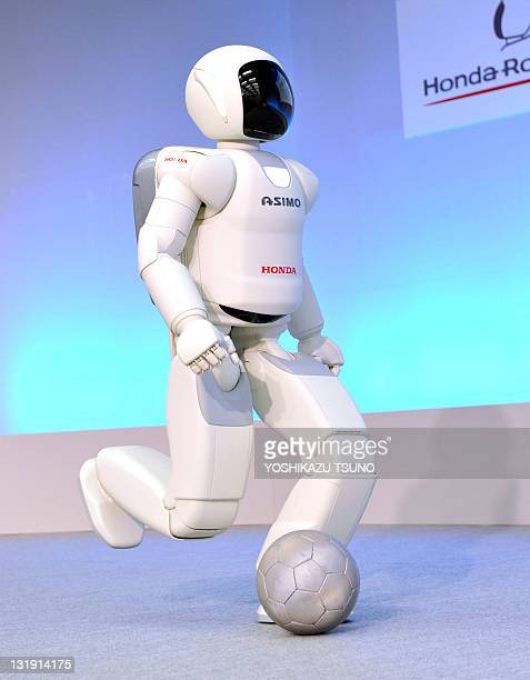 A Honda robot named 'Asimo' kicks a ball during a demonstration of its new fuctions at the company's laboratory in Wako city suburban Tokyo on...