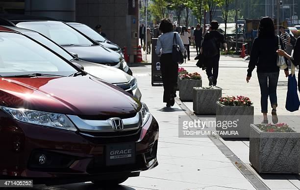 Honda vehicles are on display in front of its headquarters in Tokyo on April 28 2015 Honda said that its fiscalyear net profit fell 89 percent to 44...
