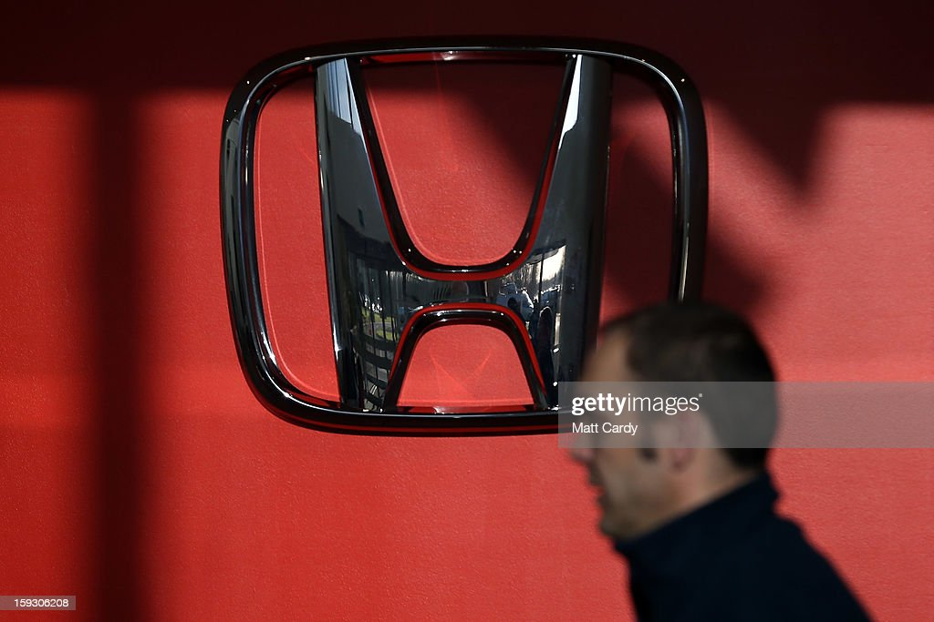A Honda worker passes a Honda logo at the Honda car assembly plant following the announcement that the firm is to axe 800 jobs on January 11, 2013 in Swindon, England. The Japanese car maker, which employs 3500 people and assembles the Civic, Jazz and CR-V models at the Wiltshire plant, blames weak demand in the Eurozone for the cuts.