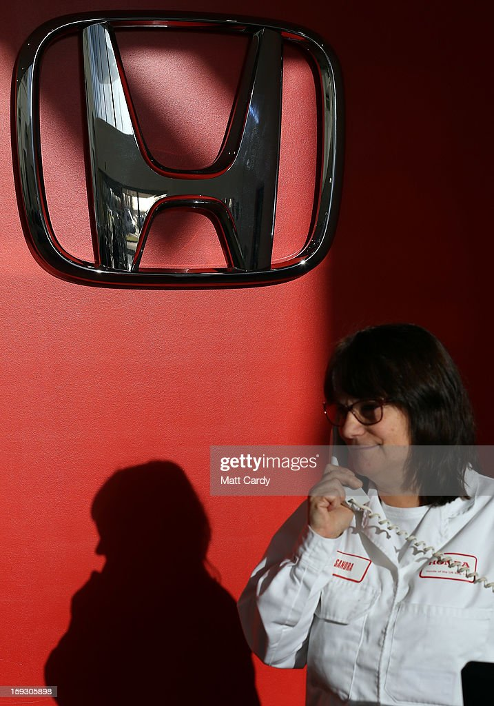 A Honda worker speaks on the telephone in the reception of a office building at the Honda car assembly plant following the announcement that the firm is to axe 800 jobs on January 11, 2013 in Swindon, England. The Japanese car maker, which employs 3500 people and assembles the Civic, Jazz and CR-V models at the Wiltshire plant, blames weak demand in the Eurozone for the cuts.