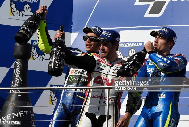 Honda's British rider Cal Crutchlow celebrates his victory with second position Movistar Yamaha MotoGP's Italian rider Valentino Rossi and third...