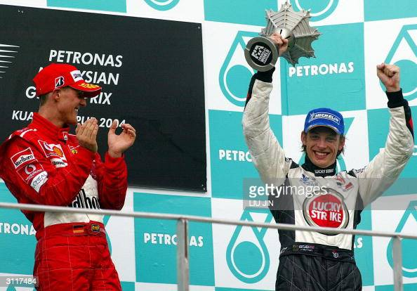 Honda's Jenson Button of Great Britian lifts his trophy as Ferrari's reigning sixtime World Champion Michael Schumacher of Germany applauds after the...