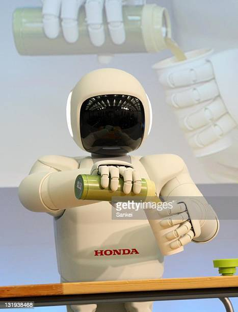 Honda's new model of humanoid robot ASIMO opens canned juice and pours into a glass on November 8 2011 in Wako Saitama Japan