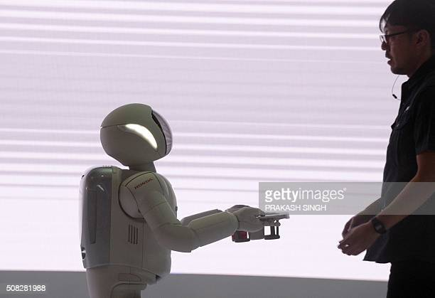 Honda's robot 'Ashimo' shows its skills by carrying a glass of water at Auto Expo 2016 in Greater Noida some 45kms east of New Delhi on February 4...