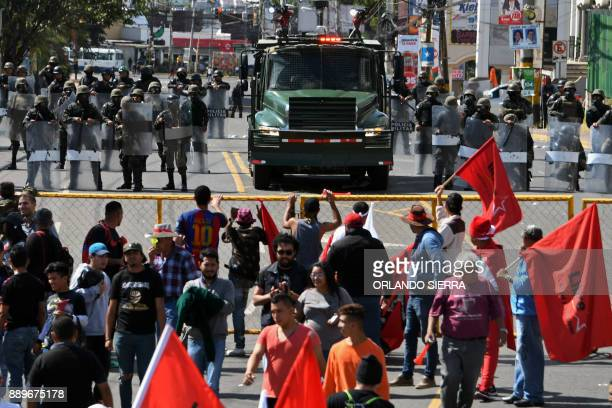 Honduran Army soldiers stand guard as supporters of presidential candidate for Honduras' Opposition Alliance against Dictatorship Salvador Nasralla...