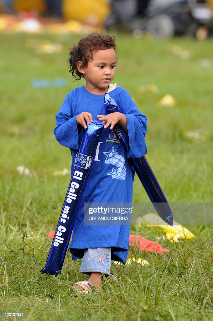 A Honduran child walks as his parents watch a FIFA World Cup Group H first round match against Chile on June 16, 2010, in San Pedro Sula, 240 km north of Tegucigalpa. Chile won 1-0. AFP PHOTO/Orlando Sierra