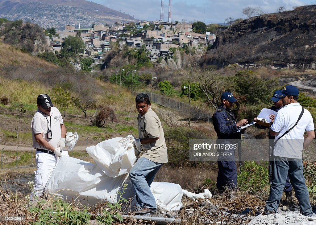 Honduran forensic personnel and policemen carry the corpses of two youngsters murdered in the surroundings of the Honduran Air Force (FAH) headquarters, in south Tegucigalpa, on February 18, 2013. AFP PHOTO/Orlando SIERRA