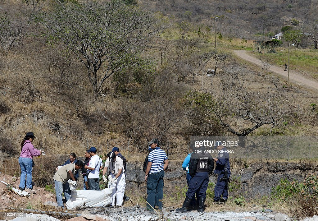 Honduran forensic personnel and policemen check the corpses of two youngsters murdered in the surroundings of the Honduran Air Force (FAH) headquarters, in south Tegucigalpa, on February 18, 2013. AFP PHOTO/Orlando SIERRA