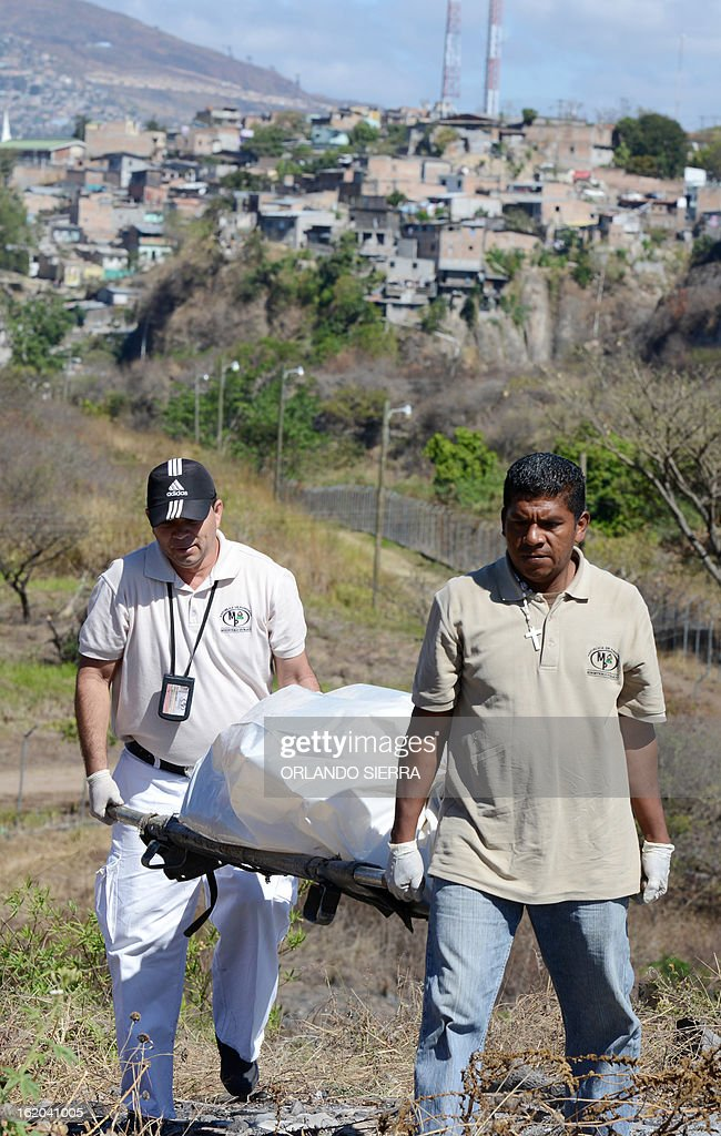 Honduran forensic personnel carry the corpses of two youngsters murdered in the surroundings of the Honduran Air Force (FAH) headquarters, in south Tegucigalpa, on February 18, 2013. AFP PHOTO/Orlando SIERRA