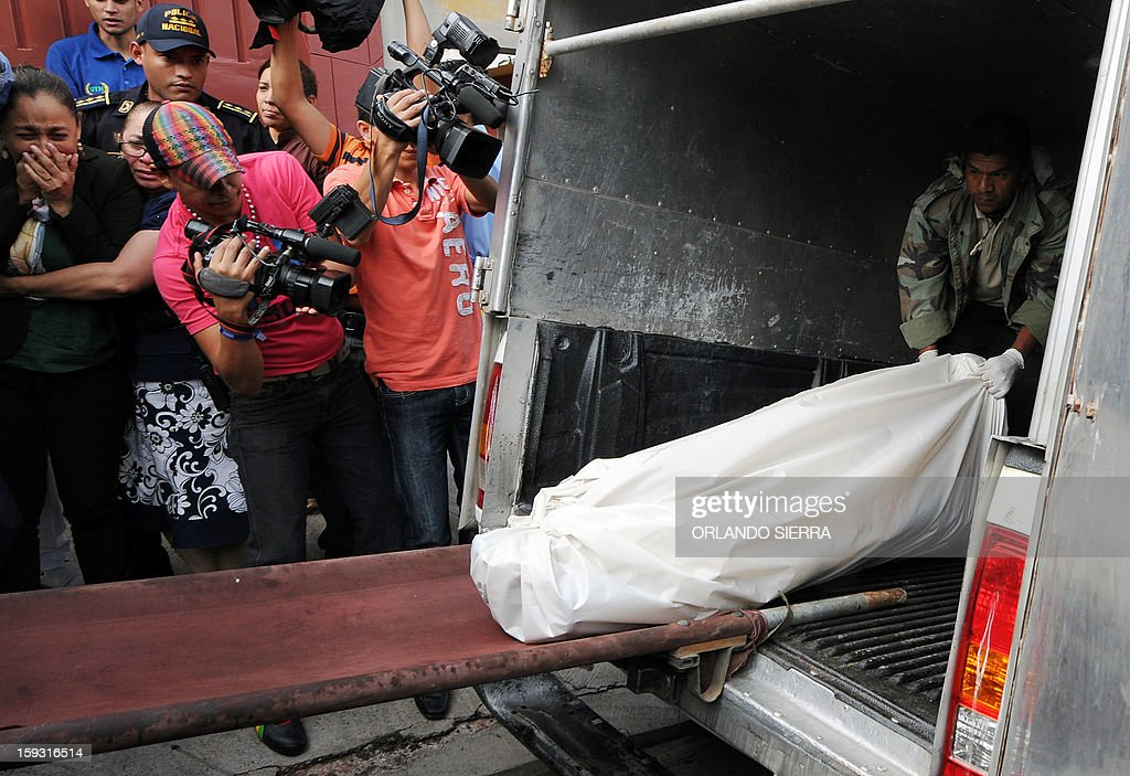 Honduran forensic staffers load onto a van the body of the vice-minister director of the National Institute for Forest Conservation and Development (ICF), Carlos Moreno, who was found dead on January 11, 2013 in Palma Real, south Tegucigalpa. AFP PHOTO /Orlando SIERRA.