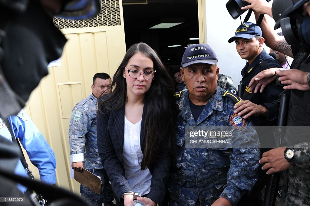 Honduran former model Ilsa Vanessa Molina (C) is escorted by policemen after being formally prosecuted and held on remand accused of assets laundering to the detriment of the the Honduran Institute of Social Security (IHSS), in Tegucigalpa, on June 27, 2016. According to the Public Ministry Molina laundered assets for more than 9.6 million lempiras (435,200 dollars) through fraudulent contracts with a fake company. / AFP / ORLANDO
