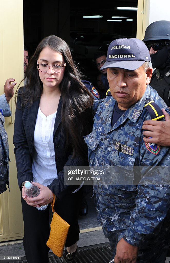 Honduran former model Ilsa Vanessa Molina (L) is escorted by policemen after being formally prosecuted and held on remand accused of laundering assets to the detriment of the the Honduran Institute of Social Security (IHSS), in Tegucigalpa, on June 27, 2016. According to the Public Ministry, Molina laundered assets for more than 9.6 million lempiras (435,200 dollars) through fraudulent contracts with a fake company. / AFP / ORLANDO