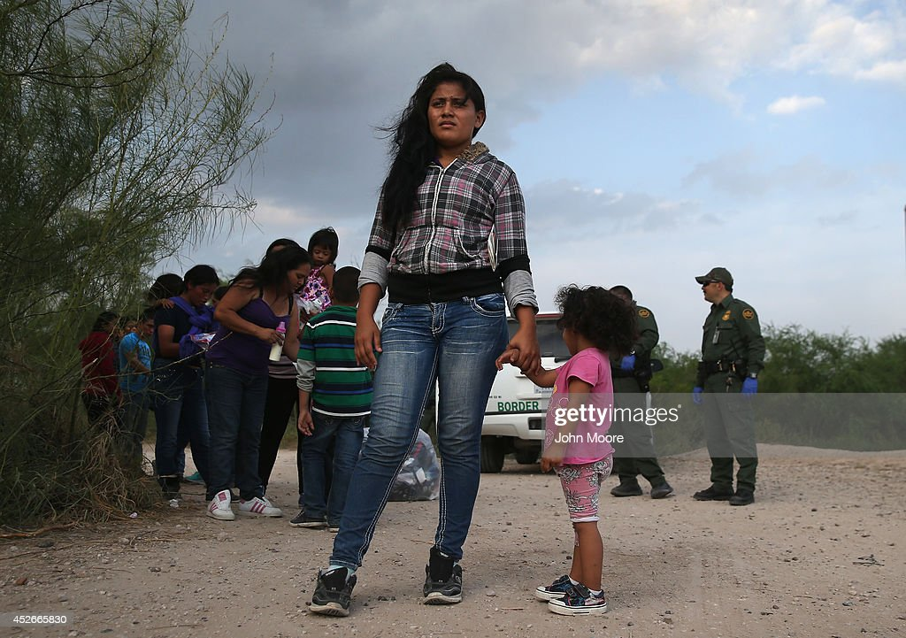 Honduran immigrants Maria Celeste Castro and her daughter Melida Patricio wait as a Border Patrol vehicle arrives to transport their group to a...