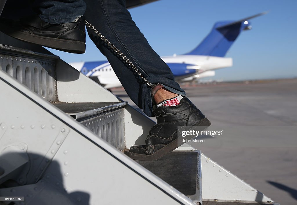 A Honduran immigration detainee, his feet shackled and shoes laceless as a security precaution, boards a deportation flight to San Pedro Sula, Honduras on February 28, 2013 in Mesa, Arizona. U.S. Immigration and Customs Enforcement (ICE), operates 4-5 flights per week from Mesa to Central America, deporting hundreds of undocumented immigrants detained in western states of the U.S. With the possibility of federal budget sequestration, ICE released 303 immigration detainees in the last week from detention centers throughout Arizona. More than 2,000 immigration detainees remain in ICE custody in the state. Most detainees typically remain in custody for several weeks before they are deported to their home country, while others remain for longer periods while their immigration cases work through the courts.