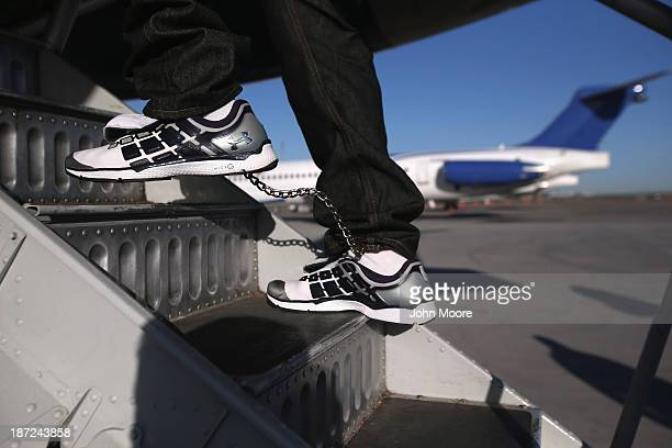Honduran immigration detainee his feet shackled and shoes laceless as a security precaution boards a deportation flight to San Pedro Sula Honduras on...