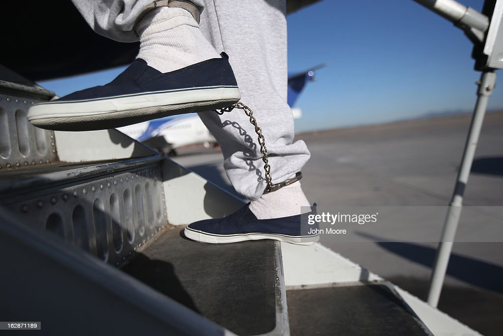 A Honduran immigration detainee, his feet shackled as a security precaution, boards a deportation flight to San Pedro Sula, Honduras on February 28, 2013 in Mesa, Arizona. U.S. Immigration and Customs Enforcement (ICE), operates 4-5 flights per week from Mesa to Central America, deporting hundreds of undocumented immigrants detained in western states of the U.S. With the possibility of federal budget sequestration, ICE released 303 immigration detainees in the last week from detention centers throughout Arizona. More than 2,000 immigration detainees remain in ICE custody in the state. Most detainees typically remain in custody for several weeks before they are deported to their home country, while others remain for longer periods while their immigration cases work through the courts.