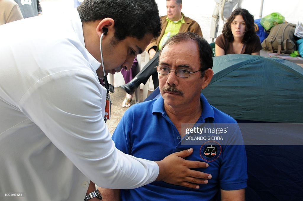 Honduran judge Luis Alonso Chevez (R), who with judge Adan Guillermo Lopez are on hunger strike since seven days ago, is checked up by a doctor at La Merced square in Tegucigalpa, May 24, 2010. Both judges were dismissed by the Supreme Court of Justice for having condemned the June 28, 2009's coup against President Manuel Zelaya. AFP PHOTO/Orlando SIERRA.
