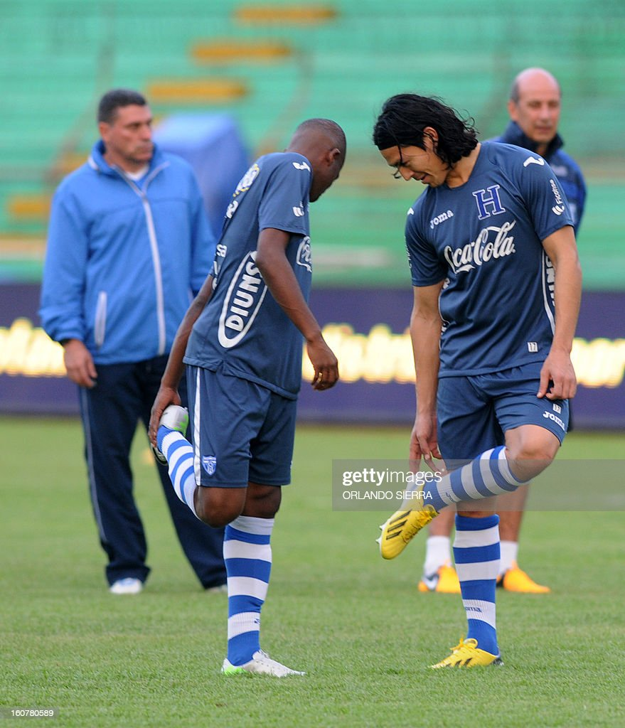 Honduran national football team players Bonieck Garcia (L) and Roger Espinoza (R), look at their shoes during a training session at the Olimpico Metropolitano stadium, in San Pedro Sula, 240 km north of Tegucigalpa, on February 5, 2013. Honduras will face the US on Wednesday in a WC2014 Concacaf qualifier football match. AFP PHOTO/Orlando SIERRA