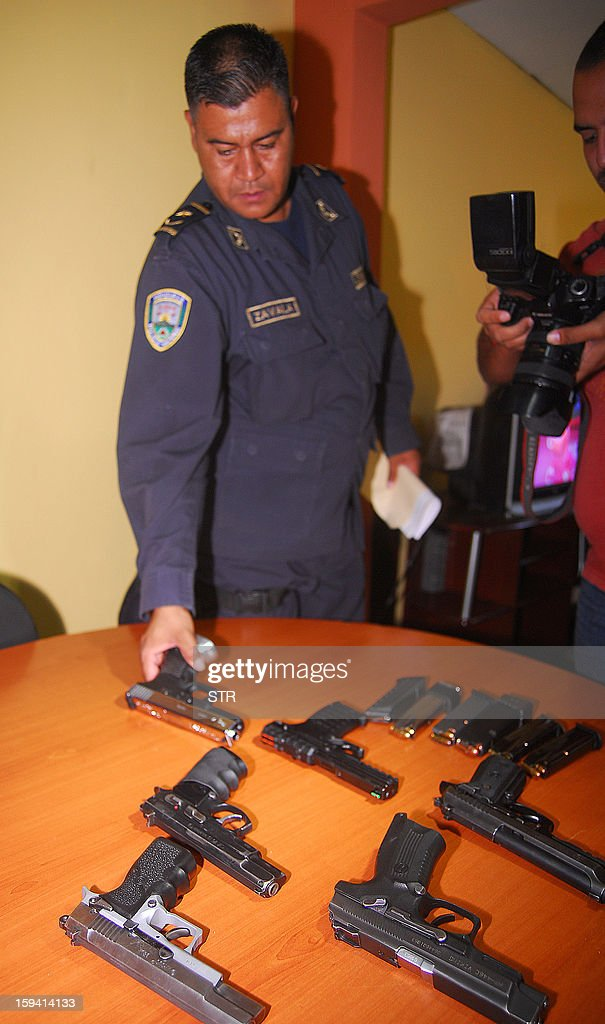 A Honduran police officer displays weapons siezed from Guatemalan deputy Leslie Elisa Bueso of the Union of National Change party and her entourage in San Pedro Sula, 180 kms north off Tegucigalpa, on January 13, 2013. Bueso was detained alongside her husband and four bodyguards, for carrying numerous guns without the proper permits.