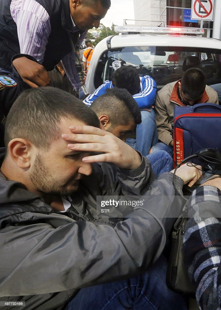 A Honduran policeman stands next to four of five Syrian citizens arrested at the Tocontin international airport in Tegucigalpa on November 18 2015...
