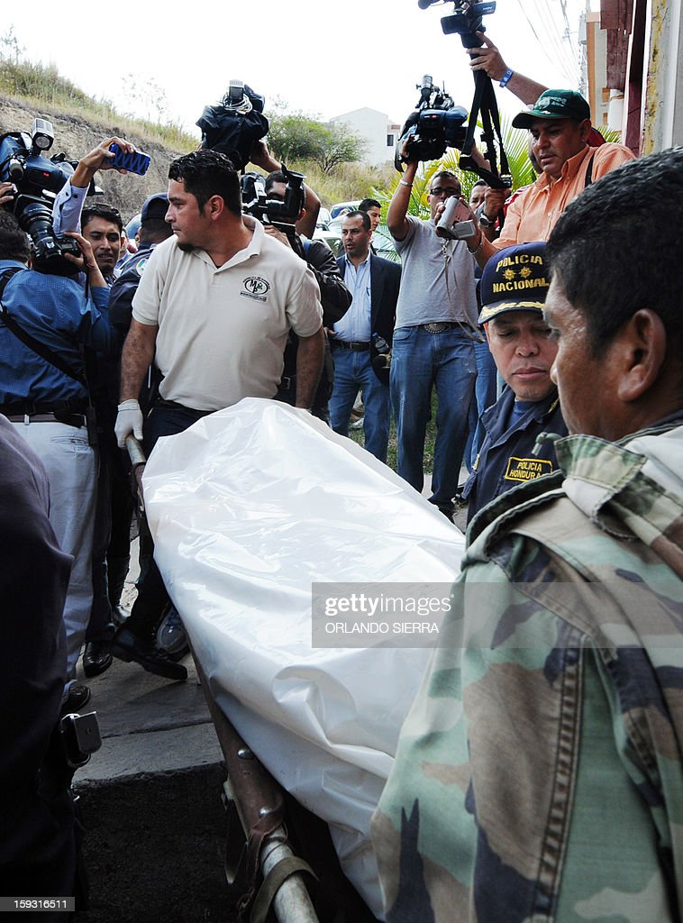 Honduran policemen and forensic staffers carry the body of the vice-minister director of the National Institute for Forest Conservation and Development (ICF), Carlos Moreno, who was found dead on January 11, 2013 in Palma Real, south Tegucigalpa. AFP PHOTO /Orlando SIERRA.