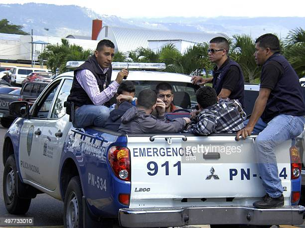 Honduran policemen escort five Syrian citizens arrested at the Tocontin international airport in Tegucigalpa on November 18 2015 Honduran authorities...