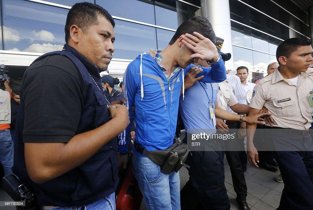 Honduran policemen escort one of five Syrian citizens arrested at the Tocontin international airport in Tegucigalpa on November 18 2015 Honduran...