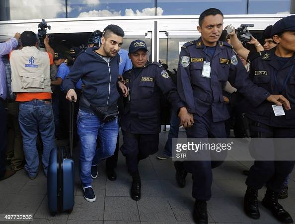 Honduran policemen escort one of five Syrian citizens arrested at the Tocontin international airport in Tegucigalpa on November 18 2015 Honduran...