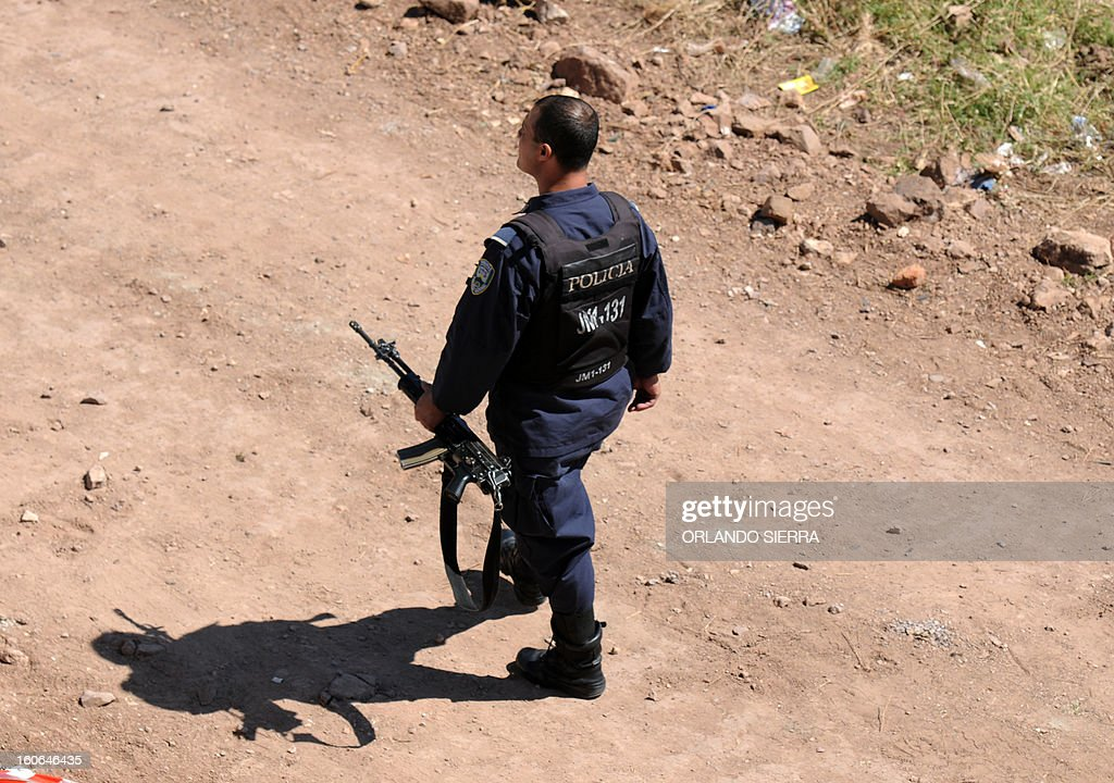 A Honduran policemen patrols the area where two men were killed in a poor suburb under the 'maras' (youth gangs) rule, in Tegucigalpa, on February 4, 2013. Honduran police has tightened security operations in neighbourhoods where the 'maras' --specially M18 and M13-Salvatrucha-- are operating and hold a 'virtual curfew'. AFP PHOTO/Orlando SIERRA.