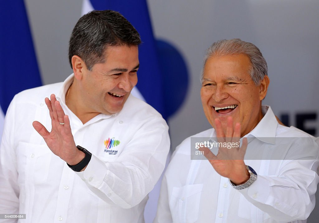 Honduran President Juan Orlando Hernandez and Salvadorean President Salvador Sanchez Ceren wave during the family photo of the XLVII SICA ordinary meeting of Heads of State and Government in Roatan island, Honduras, on June 30, 2016. / AFP / STR