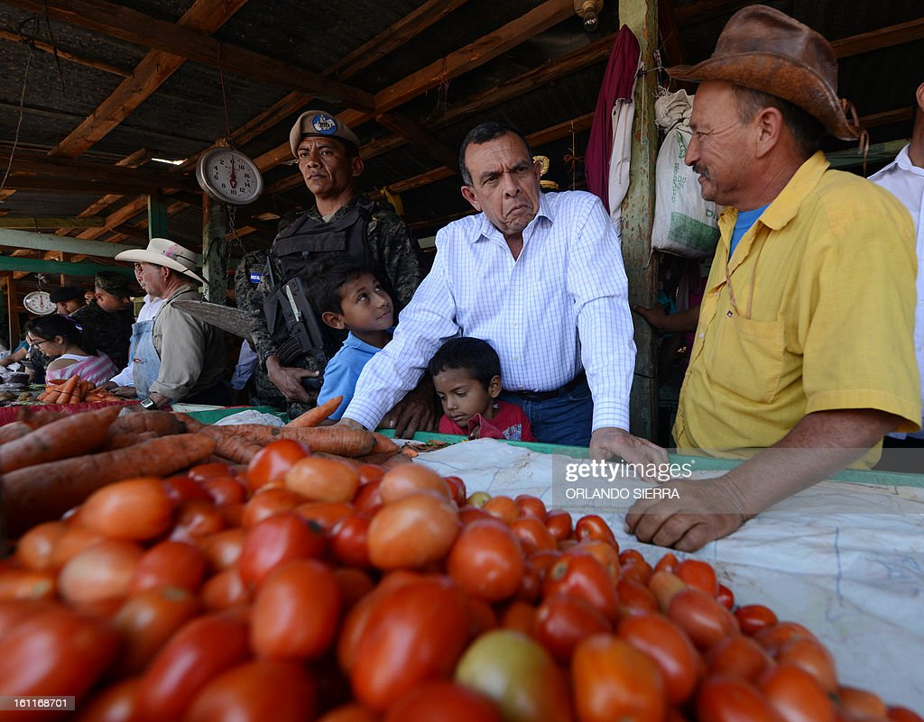 Honduran President Porfirio Lobo (C) talks with a vegetable vendor in Tegucigalpa on February 9, 2013 as he supervises a joint operation between the Army and the National Police to combat the high crime rates in the country, which has the world's highest murder rate. Operation Freedom is being carried out in Tegucigalpa as well as in San Pedro Sula which according to a recent statement by the US State Department 'is considered to be the world's most violent city, with 159 murders for every 100,000 residents in 2011.' AFP PHOTO/Orlando SIERRA