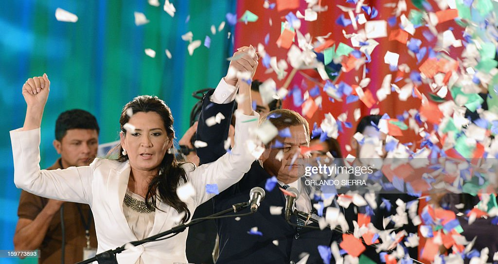 Honduran retired General Romeo Vasquez Velasquez (R) and his wife Licida Zelaya Lobo raise hands after lauching his candidacy to the Honduran Presidency for the Honduran Patriotic Alliance in Tegucigalpa, on January 20, 2013. Vasquez was head of the Armed Forces of Honduras from January 11, 2005 to January 25, 2010. AFP PHOTO / Orlando SIERRA