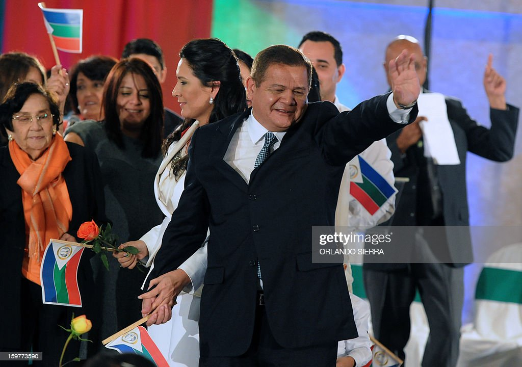 Honduran retired General Romeo Vasquez Velasquez (R) waves next to his wife Licida Zelaya Lobo after lauching his candidacy to the Honduran Presidency for the Honduran Patriotic Alliance in Tegucigalpa, on January 20, 2013. Vasquez was head of the Armed Forces of Honduras from January 11, 2005 to January 25, 2010. AFP PHOTO / Orlando SIERRA
