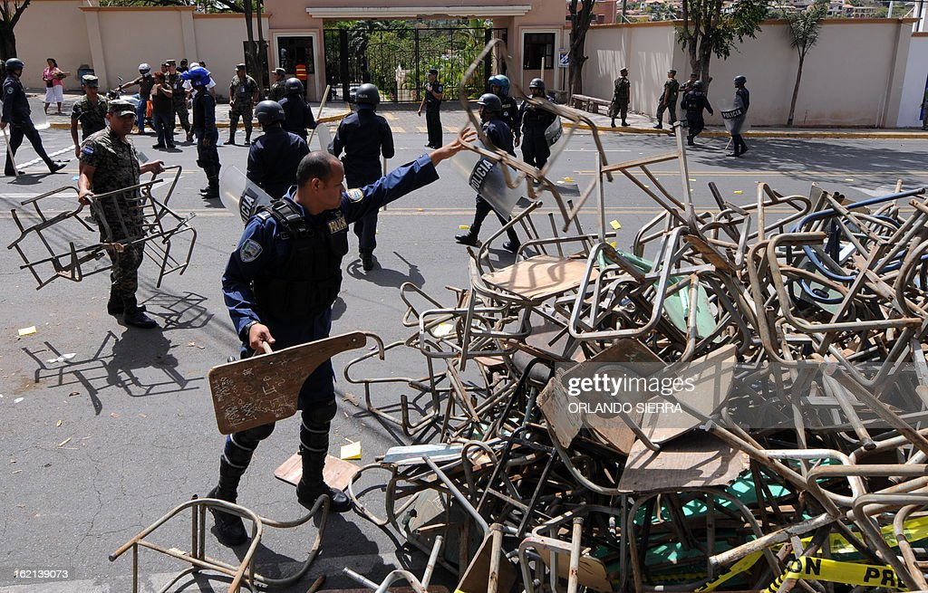 Honduran riot policemen and soldiers take broken desks out of the Juan Pablo II boulevard --which goes past the Government House-- during a teachers protest against Porfirio Lobo's government demanding their salaries pay and better infrastructure, in Tegucigalpa, on February 19, 2013. AFP PHOTO/Orlando SIERRA