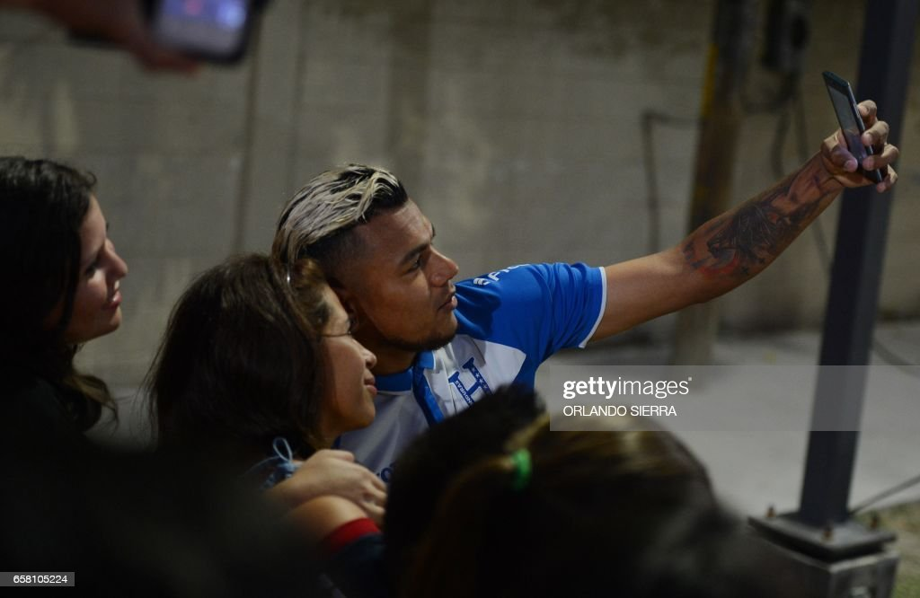 Honduras' football team player Mario Martinez poses for a selfie with residents of Chamelecon -domain of Mara Salvatrucha (MS13) and Barrio 18 gangs- during an activity to raise their spirits after losing 6-0 to the United States and ahead of their upcoming match against Costa Rica in the FIFA World Cup Concacaf qualifiers, in the outskirts of San Pedro Sula, north of Tegucigalpa, on March 26, 2017. SIERRA