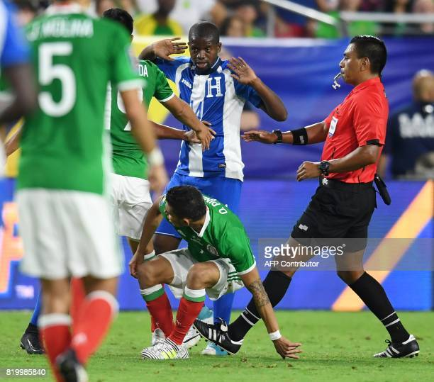 Honduras midfielder Oscar Boniek Garcia reacts after colliding with Mexico's Orbelin Pineda during thier quarterfinal CONCACAF Gold Cup match July 20...