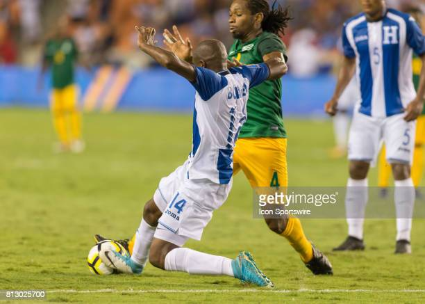 Honduras midfielder Oscar Boniek Garcia slides to win the ball from French Guiana forward Rhudy Evens during the CONCACAF Gold Cup Group A match...