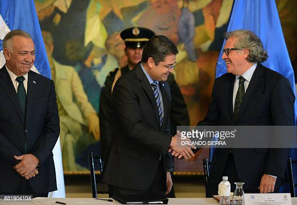 Honduras' President Juan Orlando Hernandez shakes hands with Secretary General of the Organization of American States Luis Almagro next to the...