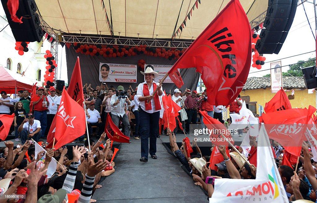 Honduras presidential candidate for the Libertad y Refundacion party (LIBRE), Xiomara Castro (C) waves a flag during a campaign rally in Gracias, Lempira, 200 km west of Tegucigalpa on October 26, 2013. Honduras will hold general elections next November 24. AFP PHOTO / Orlando SIERRA