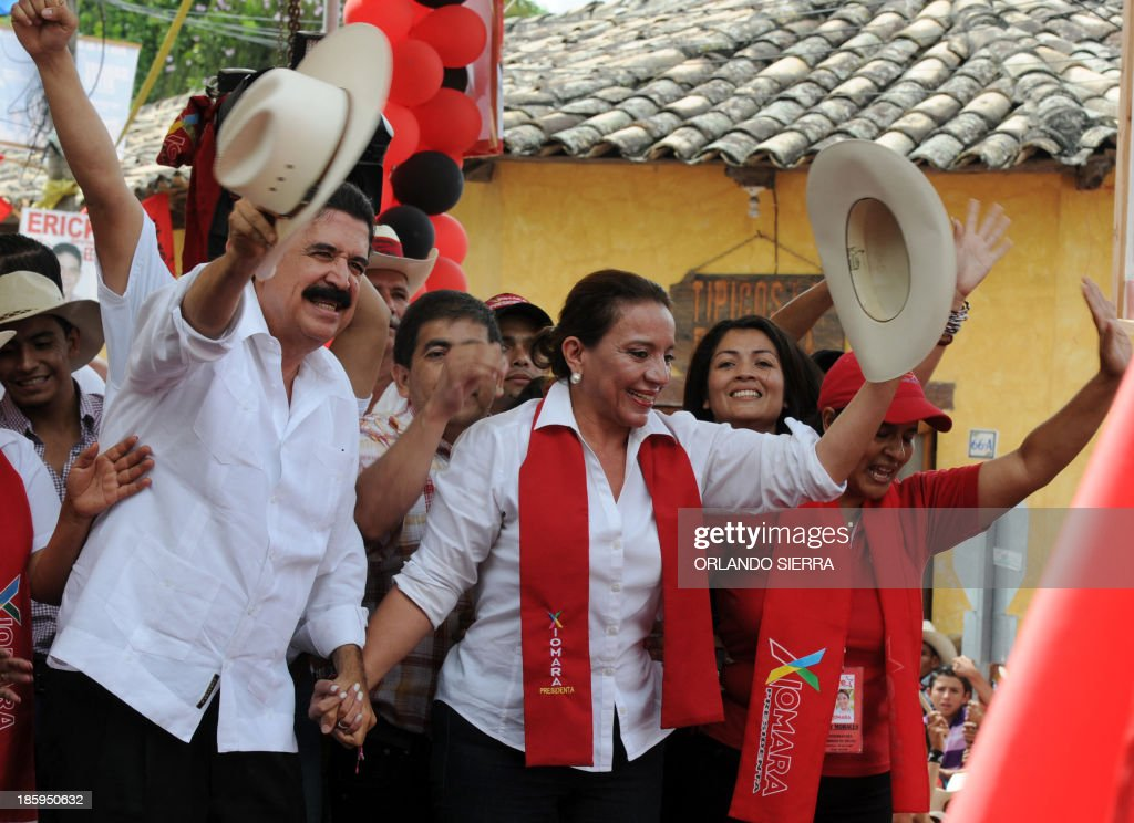 Honduras' presidential candidate for the Libertad y Refundacion party (LIBRE), Xiomara Castro (C) and her husband former Honduran president Manuel Zelaya (L) wave to supporters during a campaign rally in Gracias, Lempira, 200 km west of Tegucigalpa, on October 26, 2013. Honduras will hold general elections next November 24. AFP PHOTO / Orlando SIERRA
