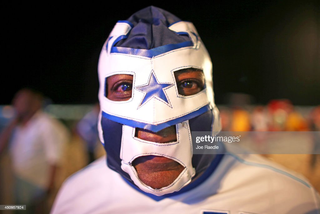 A Honduras soccer team fan wears a mask while watching the game against Ecuador on the screen setup at the Word Cup FIFA Fan Fest during on Copacabana beach on June 20, 2014 in Rio de Janeiro, Brazil.