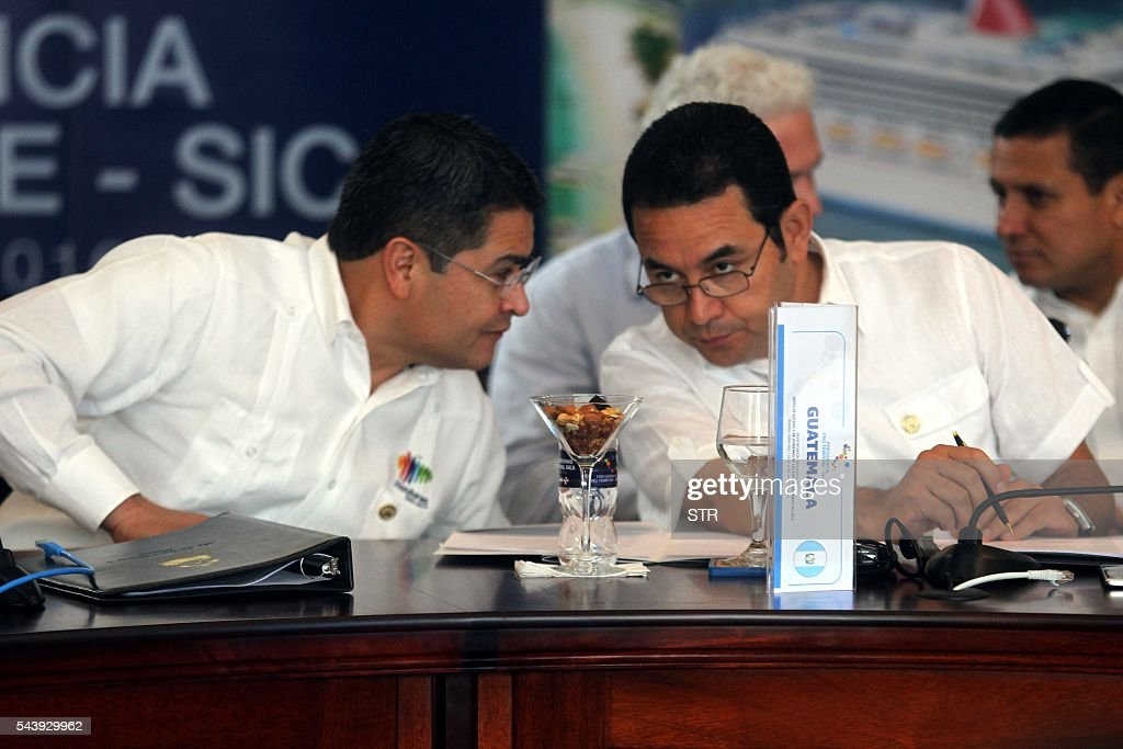 Hondurean President Juan Orlando Hernandez (L) speaks with his Guatemalan counterpart Jimmy Morales during the XLVII Ordinary Meeting of the chiefs of state members of the Central American Integration System (SICA) in Roatan island, Honduras, on June 30, 2016. Belize, Costa Rica, El Salvador, Guatemala, Honduras, Nicaragua, Panama and Dominican Republic are members of the SICA. / AFP / STR