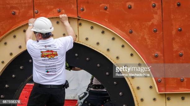 Honest Ed's store sign is removed by a Pattison Sign crew Worker holding a piece of the sign as it is lowered The traditional Toronto landmark and...