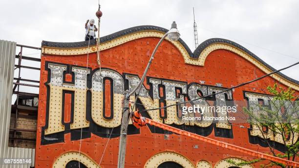 Honest Ed's store sign is removed by a Pattison Sign crew Worker on the roof tying ropes to lower the second piece of the iconic sign The traditional...