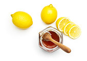 Honey and fresh lemon over white background