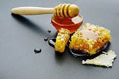 honey bee flows out of honeycomb on a black background, wooden spoon for honey