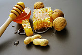 honey bee flows out of honeycomb on a black background, wooden spoon for honey and nuts