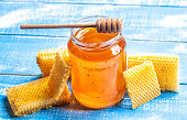jar of honey with wooden honey dipper and honeycomb on white background