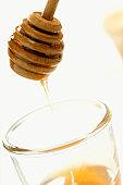 Honey dipper above jar of honey, close-up tilt